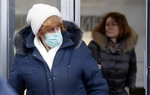 epa05154045 A picture made available 11 February 2016 shows a woman wearing a mask on her face to protect from flu while walking in a street in Moscow, Russia, 10 February 2016. Influenza swept Russia having reached epidemic levels in 74 regions. Some improvement in the situation has been noted in some regions.  EPA/MAXIM SHIPENKOV